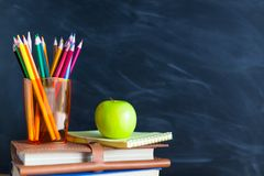 Back to School cocept. Still life with school books, pencils and. Apple against blackboard background. Close up stock photography