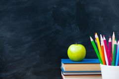 Back to School cocept. Still life with school books, pencils and. Apple against blackboard background. Close up royalty free stock photography