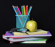 Back to school concept. An apple, colored pencils and glasses on pile of books over black. Background royalty free stock photo
