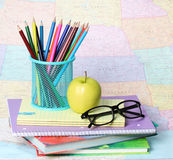 Back to school concept. An apple, colored pencils and glasses on pile of books over map Stock Photos
