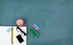 Back to school concept with basic stationery on a green chalkboard background royalty free stock photo