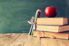 Back to school concept. Blackboard with books and apple Royalty Free Stock Image