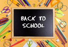 Back to school concept with blackboard and school supplies on ye. Llow background. Top view Stock Image