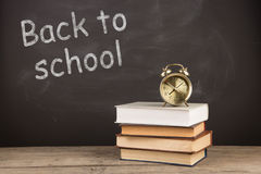Back to school concept - books on the desk over the blackboard royalty free stock photo
