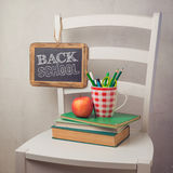 Back to school concept with books, pencils in cup and chalkboard Royalty Free Stock Images