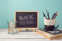 Back to school concept with books, pencils in cup and chalkboard Royalty Free Stock Photos