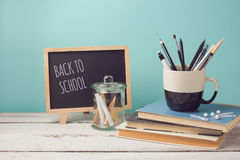 Back to school concept with books, pencils in cup and chalkboard on wooden white table Stock Photos