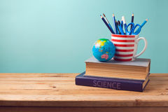 Back to school concept with books, pencils in cup and globe Royalty Free Stock Photography