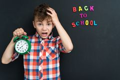 Back to school concept. Boy with big green alarm clock at the black chalkboard in classroom Stock Photo