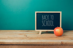 Back to school concept with chalkboard and apple on wooden table Royalty Free Stock Images