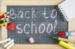 Back to school concept with chalkboard and school supplies. School supplies on a chalkboard with text `Back to school` close up Stock Image
