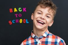 Back to school concept. Cheerful schoolboy at the black chalkboard in classroom Stock Photos