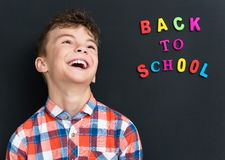 Back to school concept. Cheerful schoolboy at the black chalkboard in classroom Stock Photo