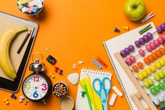 Back to school concept with clock color chalk pencil apple notebook over chalkboard background. Stock Photography