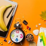 Back to school concept with clock color chalk pencil apple notebook over chalkboard background. Copy space. Top view. Flat lay Stock Images