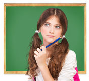 Back to school concept. Closeup portrait of cute girl standing near chalkboard and try to remember answer on question, passing exam, back to school concept Stock Photos