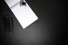Back to school concept with colour pencils, ink bottle and notepad on black background Royalty Free Stock Photo