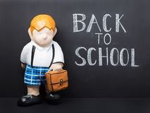 Back to school concept cute dummy. Back to school concept. Cute dummy with bag on black chalkboard background royalty free stock images
