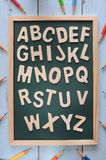 Back to school concept and education idea. Wooden alphabet letters on blackboard with coloured pencil, education concept and back to school idea Stock Image