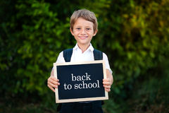 Back to school concept. Elementary school student boy holding blackboard background. Cute caucasian primary grade pupil. Cute smiling schoolboy in uniform Royalty Free Stock Photography