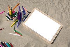 Back to school concept end of holidays white blank empty billboard on sand beach with pencil. A Back to school concept end of holidays white blank empty royalty free stock images