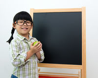 Back to school concept. School girl wearing big spectacles posing next to a blackboard Stock Photos