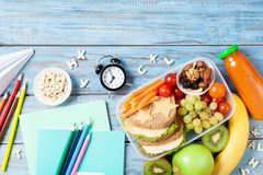 Back to school concept. Healthy lunch box and colorful stationery on turquoise wooden table top view. Royalty Free Stock Images