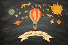Back to school concept. Hot air balloon, space elements shapes cut from paper and painted over classroom blackboard background. stock photos