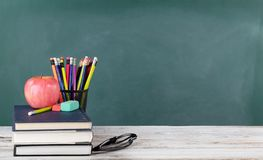 Back to school concept including books and stationery supplies with green chalkboard in background stock photo