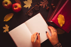 Back to school concept. Open notebook top view on the pile of bo. Back to school concept. Left-hander woman writes, Open notebook top view on the pile of books Stock Photography