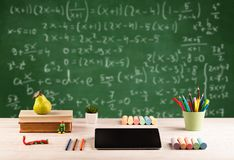 Math class from student school desk. Back to school concept with long numbers calculation on blackboard and a desk with books, fruit Royalty Free Stock Photo