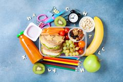 Back to school concept. Nutritional lunch box and colorful stationery on blue table top view. Back to school concept. Nutritional lunch box and colorful stock image
