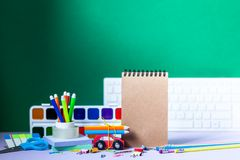 Back to school concept. School and office supplies, colorful pens, pencils, paints on green background. Back to school concept. School and office supplies royalty free stock images