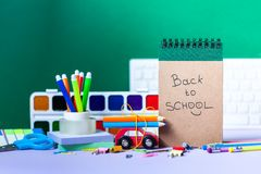Back to school concept. School and office supplies, colorful pens, pencils, paints on green background. Back to school concept. School and office supplies stock photos