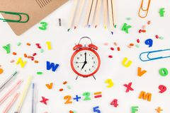Back to school concept with office supplies. Creative flat lay back to school concept with alarm clock, color school and office supplies on white table stock image