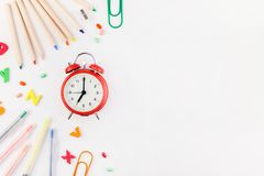 Back to school concept with office supplies. Creative flat lay back to school concept with alarm clock, color school and office supplies on white table royalty free stock images