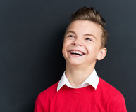 Back to school concept. Photo of adorable young happy boy looking up at the black chalkboard in classroom Royalty Free Stock Images