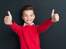 Back to school concept. Portrait of adorable young boy showing thumbs up sign using both hands at the black chalkboard in classroom Royalty Free Stock Photography