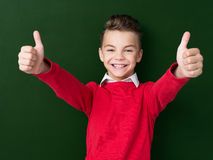 Back to school concept. Portrait of adorable young boy showing thumbs up sign using both hands at the dark green chalkboard in classroom Royalty Free Stock Photography
