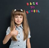 Back to school concept. Portrait of adorable young girl showing thumb up sign at the black chalkboard in classroom Royalty Free Stock Images