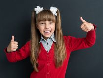 Back to school concept. Portrait of adorable young girl showing thumbs up sign using both hands at the black chalkboard in classroom Stock Photos