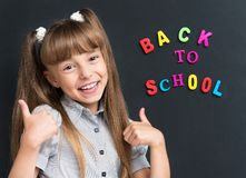Back to school concept. Portrait of adorable young girl showing thumbs up sign using both hands at the black chalkboard in classroom Stock Images
