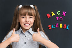 Back to school concept. Portrait of adorable young girl showing thumbs up sign using both hands at the black chalkboard in classroom Royalty Free Stock Photo