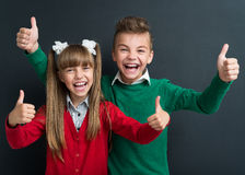 Back to school concept. Portrait of cheerful young boy and girl showing thumbs up sign at the black chalkboard in classroom Royalty Free Stock Photo