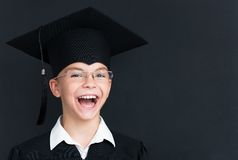 Back to school concept. Portrait of happy pupil in mortar board and eyeglasses smiling at camera in classroom Stock Photos