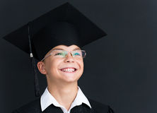 Back to school concept. Portrait of happy pupil in mortar board and eyeglasses smiling at camera in classroom Stock Photography