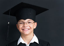 Back to school concept. Portrait of happy pupil in mortar board and eyeglasses smiling at camera in classroom Royalty Free Stock Photography