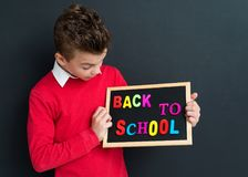 Back to school concept. Portrait of happy young student with small blackboard. Cute pupil - teen boy at the black chalkboard background in classroom Stock Image