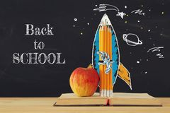 Back to school concept. rocket sketch and pencils over open book in front of classroom blackboard. stock illustration