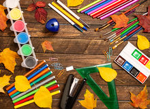 Back to school concept. School supplies and autumn leaves on rustic wooden background. royalty free stock photo